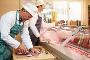 two butchers preparing meat in a butcher shop